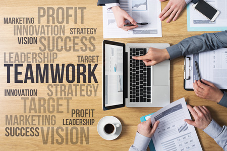 Business team hands at work with financial reports and a laptop, marketing and strategy concepts on the left, top view