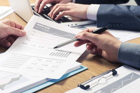 Les professionnels qui travaillent ensemble au bureau, les mains se referment soulignant données financières sur un rapport
