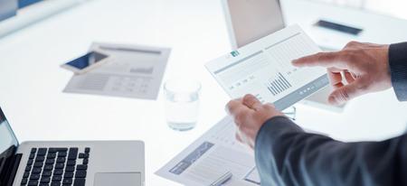 Business team werken op kantoor bureau en onderzoekt financiële gegevens op een touchscreen-apparaat, handen close up Stockfoto