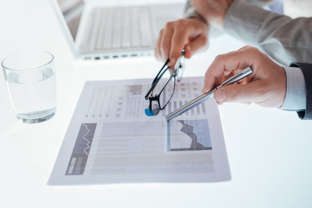unrecognizable people: Business team examining a financial report and pointing to a chart, hands close up, unrecognizable people Stock Photo