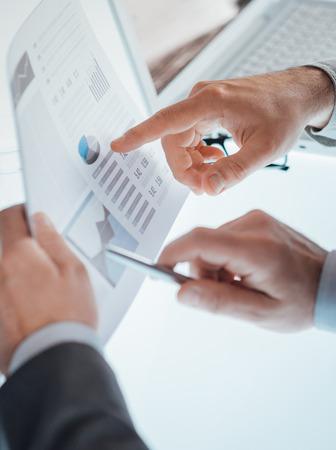 D'affaires discuter ensemble sur un rapport financier et pointant vers un tableau, les mains se referment professionnel, ordinateur portable et de bureau sur fond