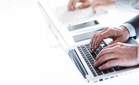 unrecognizable people: Professional businessmen working on laptops at office desk, hands close up, unrecognizable people