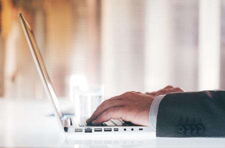 事務所の机に座って、手を閉じるまで、認識できない人、ラップトップに取り組んでプロのビジネスマン