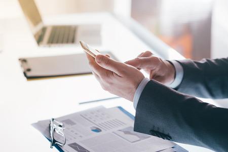Homme d'affaires dans son bureau textos avec un smartphone, ordinateur de bureau et ordinateur portable sur fond, concept de communication mobile
