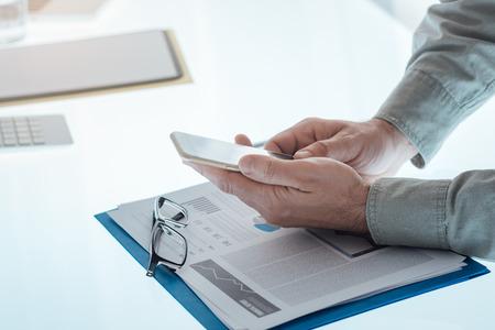 Businessman using a smartphone hands close up, unrecognizable person Stock Photo