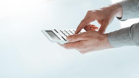 business manager: Businessmans hands using a calculator close up, white desk on background