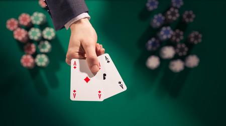 cartas de poker: Elegante jugador de póker masculino que sostiene dos ases con un montón de fichas en el fondo y el cuadro verde, vista desde arriba