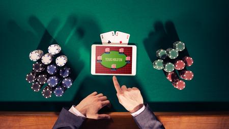 fichas casino: Manos del jugador de póker con tableta digital, pilas de fichas y las cartas sobre la mesa verde, vista desde arriba Foto de archivo