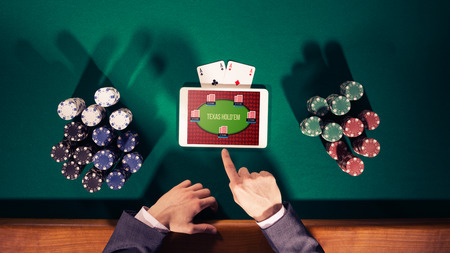 casino chips: Poker players hands with digital tablet, stacks of chips and cards on green table, top view Stock Photo