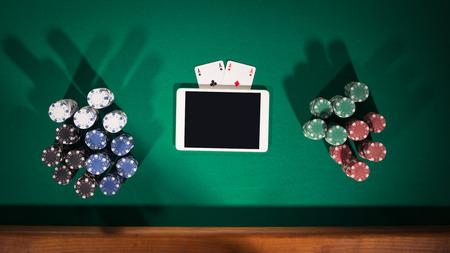 fichas casino: Online juego de póquer aplicación de concepto con la tableta, tarjetas y pilas de fichas digitales, vista desde arriba