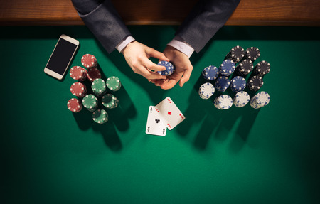 casino dealer: Elegant male poker player with smartphone holding chips, he has two ace cards, hands close up top view
