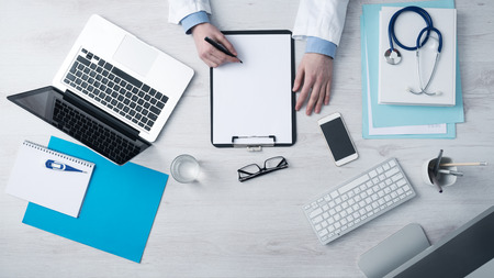 Professional doctor writing medical records on a clipboard with computer and medical equipment all around, desktop top view Stock Photo