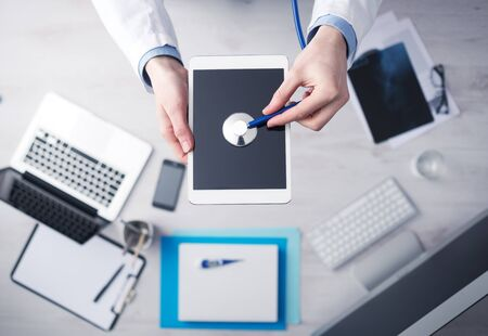 listening to heartbeat: Doctor checking heartbeat on a digital tablet using a stethoscope, desktop with medical equipment on background, top view