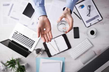 vaso con agua: Oficinista que tomar una píldora y la celebración de una copa de manos de agua de cerca con el escritorio en el fondo, vista desde arriba Foto de archivo