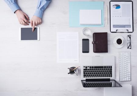 trabajo en la oficina: El hombre de negocios que trabajan en escritorio de oficina y el uso de un control digital de pantalla tablet manos detalle, equipo y objetos a la derecha, vista desde arriba