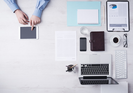 Homme d'affaires travaillant au bureau de bureau et l'aide d'un écran tactile numérique mains tablettes détail, l'ordinateur et les objets sur la droite, vue de dessus