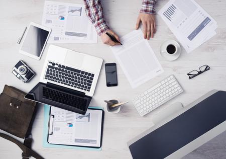 psací stůl: Obchodník pracující u stolu v kanceláři a podepisování dokumentů, počítače a papírování kolem, pohled shora