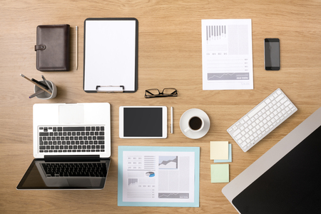 OFFICE DESK: Businessmans tidy desktop and work tools with paperwork, computer, touch screen devices and stationery on a wooden surface, top view Stock Photo