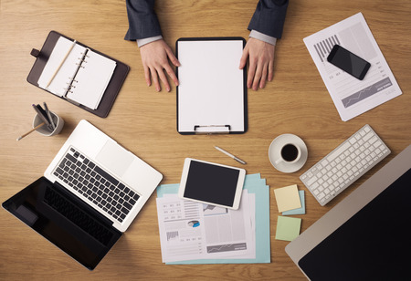 blank screen: Businessman working at office desk holding a clipboard with a blank sheet, paperwork and computers around, top view