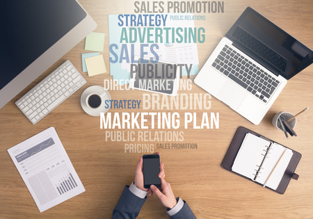 Businessman working at office desk, hands using a smart phone top view, marketing and business text concepts above desktop
