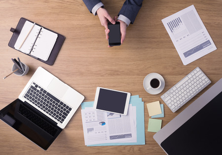Businessman working at office desk hands top view with laptop and financial reports: he is using a mobile touch screen smart phone Stock Photo - 41135735