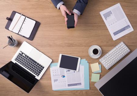 Homme d'affaires travaillant au bureau de bureau mains vue de dessus avec un ordinateur portable et des rapports financiers: il utilise un téléphone intelligent de mobile à écran tactile