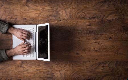 Mannelijke handen werken op een witte laptop op een houten bureaublad en kopieer de ruimte aan de rechterkant Stockfoto