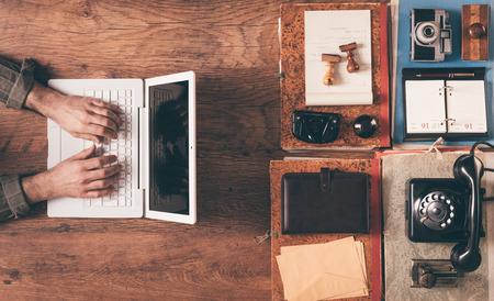 Desktop Draufsicht mit männlichen Hände Arbeit an einem modernen Laptop auf der linken und Vintage-Objekte und Elemente auf der rechten