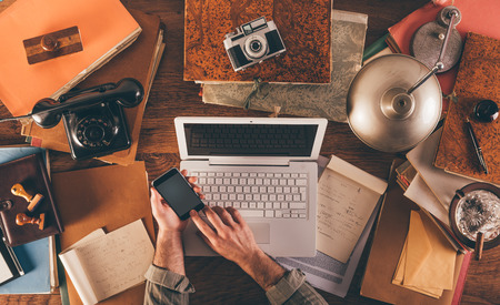 Messy vintage desktop with laptop and male hands using a smart phone, top view