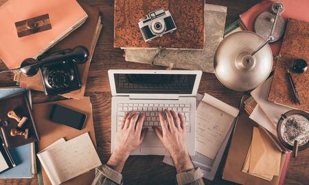 Messy bureau vintage avec un ordinateur portable et les mains des hommes dactylographie, vue de dessus