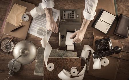 彼は、電卓を操作は、乱雑なヴィンテージ、会計士のデスクトップ マシンと紙を追加するとロール