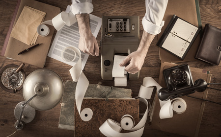 Messy vintage accountant's desktop with adding machine and paper rolls, he is working with the calculator 스톡 콘텐츠