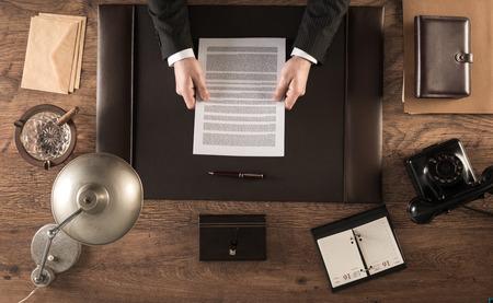 contratos: Hombre de negocios de la vendimia en la oficina de la lectura de un contrato que se sienta en su escritorio, vista desde arriba