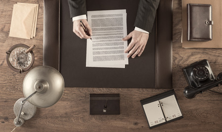 table lamp: Vintage businessman in the office reading and signing a contract sitting at his desk, top view