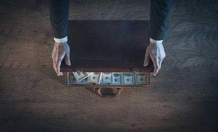 L'ouverture d'une serviette en cuir riche homme d'affaires rempli de paquets de dollars, en vue de dessus, personne méconnaissable Banque d'images - 41135806