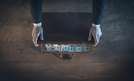 Rich businessman opening a leather briefcase filled with dollar packs, top view, unrecognizable person Imagens - 41135806