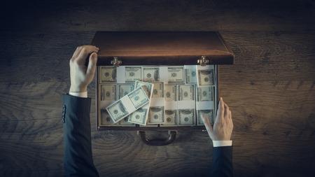 Hombre de negocios rico de abrir un maletín de cuero llena de paquetes de dólares, vista desde arriba, persona irreconocible