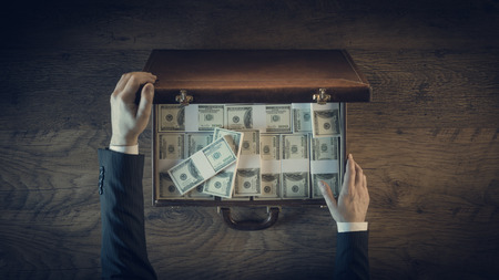 ganancias: Hombre de negocios rico de abrir un maletín de cuero llena de paquetes de dólares, vista desde arriba, persona irreconocible