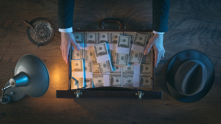 briefcase: Vintage rich businessmans desk holding a briefcase filled with dollar packs, top view