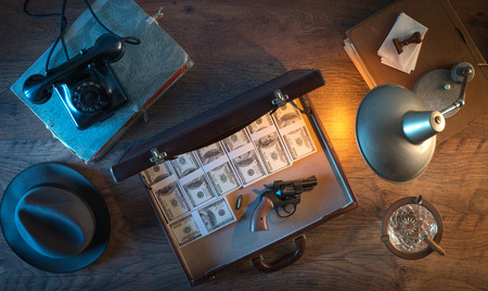 mafia: Vintage desktop in the dark with a gun, a briefcase and a lot of dollar packs, top view