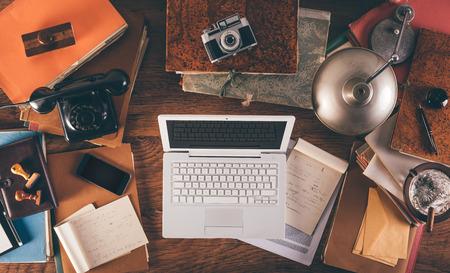 Rommelig vintage desktop met laptop, telefoon, lamp, camera en mappen, bovenaanzicht Stockfoto