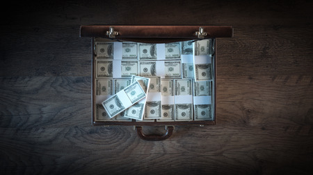 Elegant open briefcase filled with dollar packs on a wooden desktop in the dark, top view