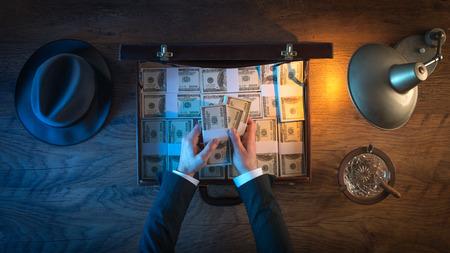 Le bureau de Vintage riche homme d'affaires avec une mallette remplie de paquets de dollars, il compte la monnaie de papier Banque d'images