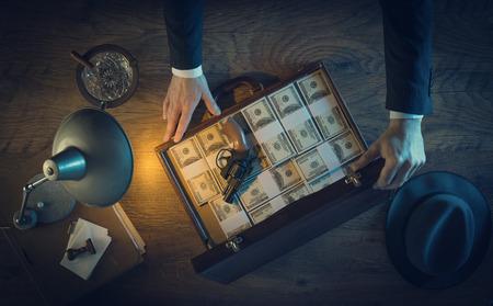 Weinlese-Gangster mit einer Pistole und einem Leder-Aktentasche mit Dollar-Packs, Ansicht von oben, 1950er Jahre Film-Noir-Stil gefüllt
