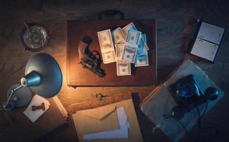 pistola: Escritorio de la vendimia en la oscuridad con una pistola, un malet�n y una gran cantidad de paquetes de d�lares, vista desde arriba