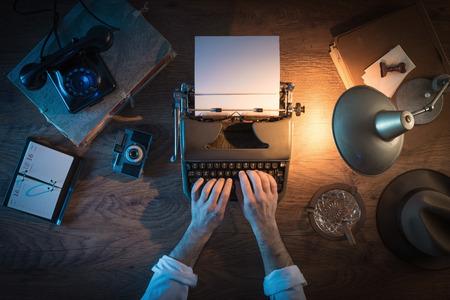 hombre escribiendo: 1950 escritorio estilo del periodista de la vendimia, que está trabajando y escribiendo en su máquina de escribir por la noche, vista desde arriba Foto de archivo