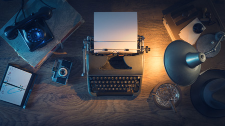 Retro journalist's desk 1950s style with vintage typewriter, phone and lamp at night time, top view 스톡 콘텐츠