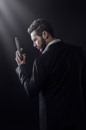 man's suit: Brave cool man holding a gun on dark background Stock Photo