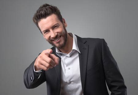 Happy smiling businessman laughing and pointing at camera Stock Photo
