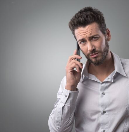 raised eyebrows: Disappointed young man on the phone having a call